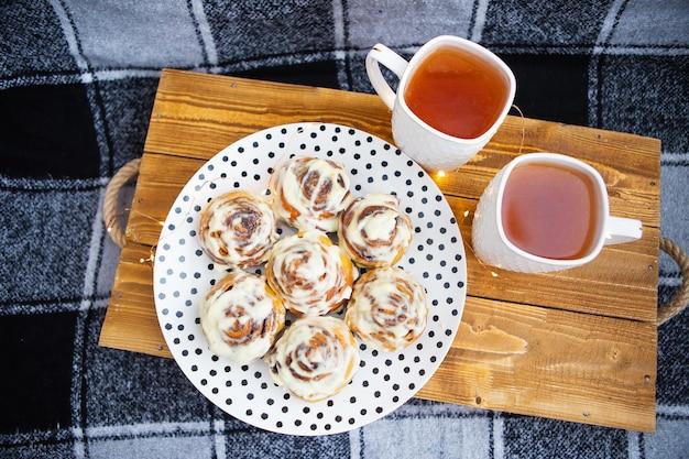Zwei tassen schwarzer tee stehen auf einem holztablett auf dem sofa mit einem schwarz-weiß karierten plaid. frische und duftende zimtschnecken liegen auf einem teller mit tupfen. die girlande blinkt