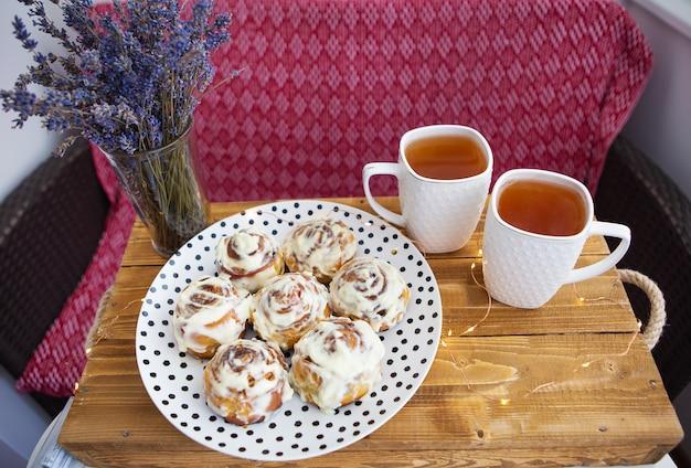 Zwei tassen schwarzer tee stehen auf einem holztablett, ein bouquet aus getrocknetem lavendel. frische und duftende zimtschnecken aus der nähe liegen auf einem teller mit tupfen, schöner morgen.