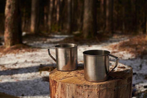 Zwei tassen tee auf dem baumstumpf im wald
