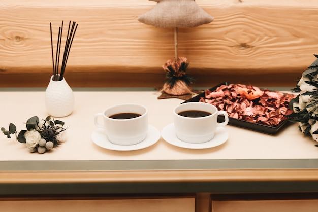 Zwei tassen tee auf einem hölzernen hintergrund in einem stilvollen innenraum