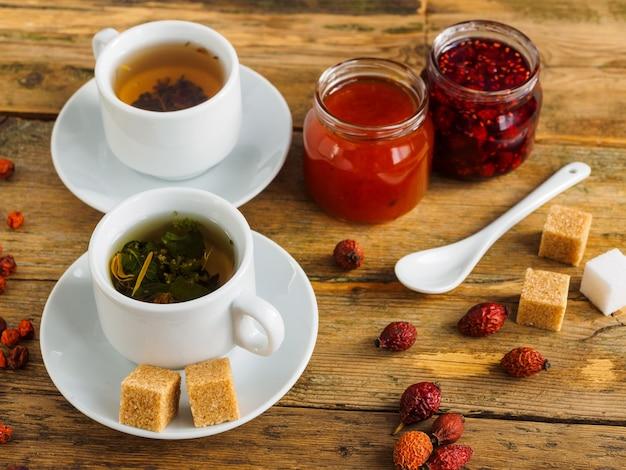 Zwei tassen tee, marmelade und trockenfrüchte auf einem holztisch