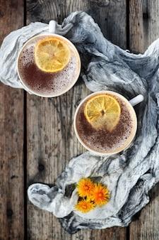 Zwei tassen tee mit zitrone auf einem rustikalen holztisch mit gänseblümchen