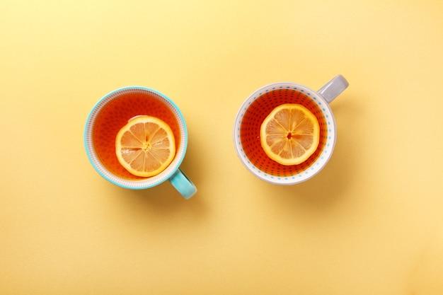 Zwei tassen tee mit zitrone auf gelbem hintergrund. draufsicht, flach lag. speicherplatz kopieren. tee für herbst oder winter.
