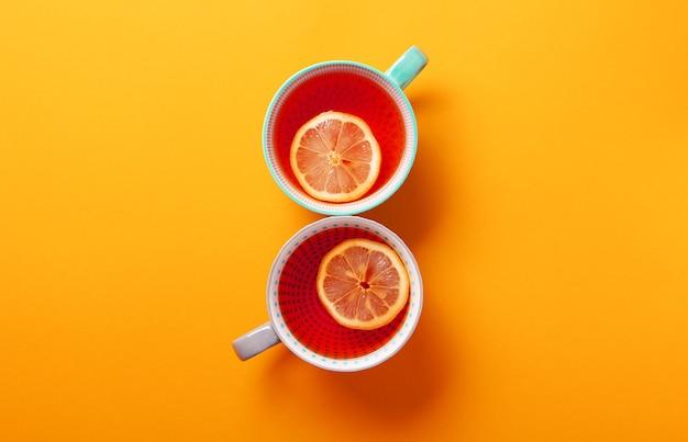 Zwei tassen tee mit zitrone auf orange hintergrund. draufsicht, flach lag. speicherplatz kopieren. tee für herbst oder winter.