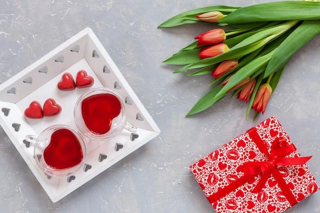 Zwei tassen tee, rote praline, geschenkbox mit rotem band und roter tulpenblumenstrauß