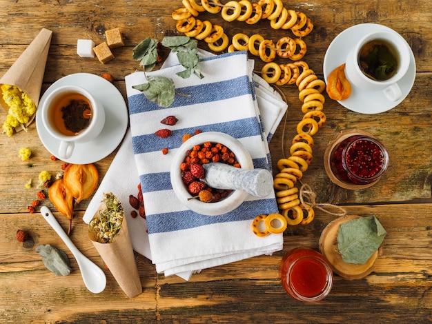 Zwei tassen tee, verschiedene marmeladen und andere süßigkeiten auf dem alten holztisch. trockenes gras.