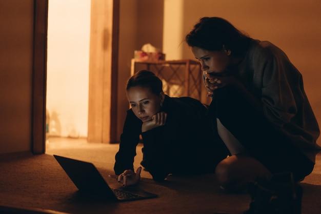 Zwei teenager, die auf linie inhalt in einem laptop liegt auf dem boden aufpassen