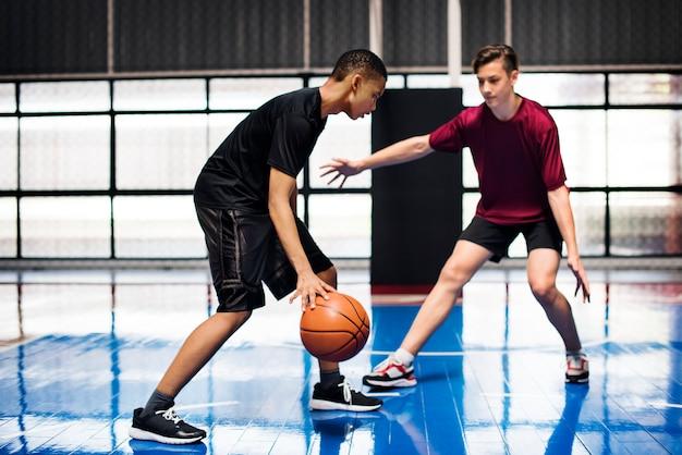 Zwei teenager, die zusammen basketball auf dem gericht spielen