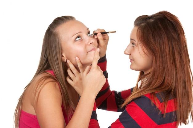 Zwei teenager färben ihre wimpern isoliert