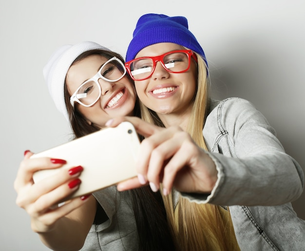 Zwei teenager-freundinnen im hipster-outfit machen selfie auf weißem hintergrund