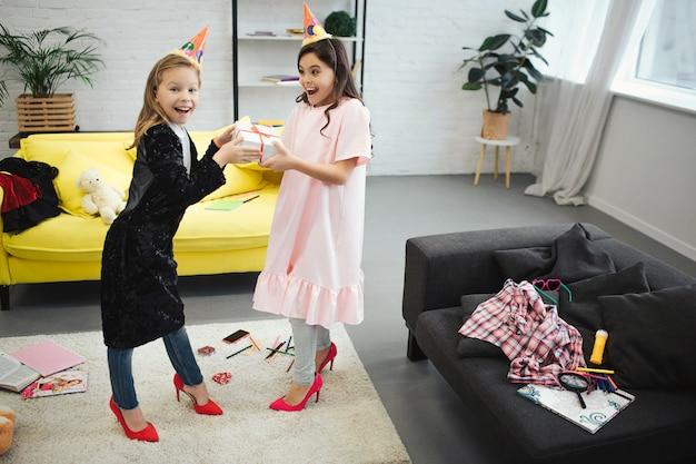 Zwei teenager haben spaß. sie stehen im raum und halten ein geschenk zusammen. mädchen tragen kleidung und schuhe für erwachsene frauen. sie haben geburtstagsfeier.