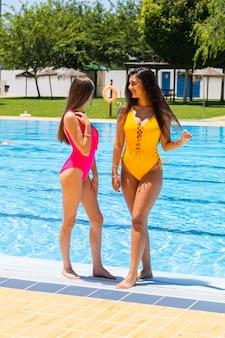 Zwei teenager in badeanzügen in einem hotelpool posieren und lächeln