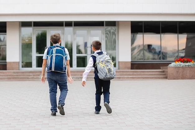 Zwei teenager in schuluniformen mit rucksäcken gehen zur schule.
