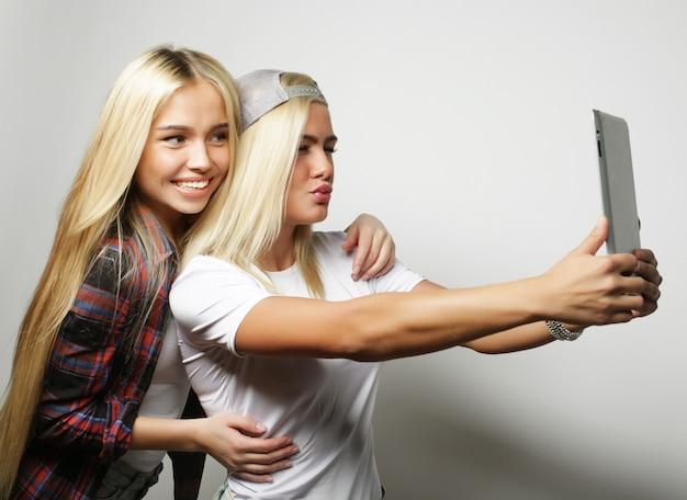 Zwei teenager-mädchen, die selfie mit tablette nehmen
