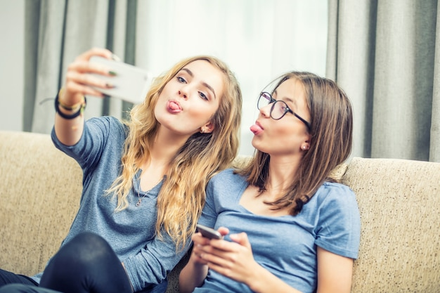 Zwei teenager-mädchen lächeln und machen zusammen ein selfie. sie machen grimassen aus ihrer zunge.