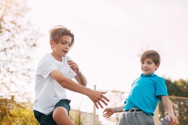 Zwei teenager spielen basketball auf dem spielplatz. die athleten kämpfen im spiel um den ball