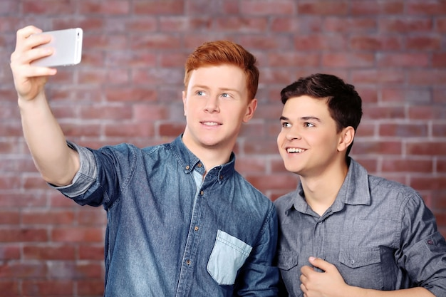 Zwei teenagerjungen, die selfie-foto mit handy machen
