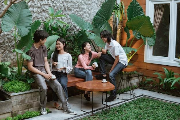 Zwei teenagerpaare plaudern und genießen einen kaffee, während sie auf tisch und holzbank im hausgarten sitzen