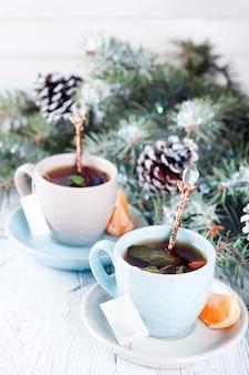 Zwei teetassen mit teebeutel und weihnachtsbaum