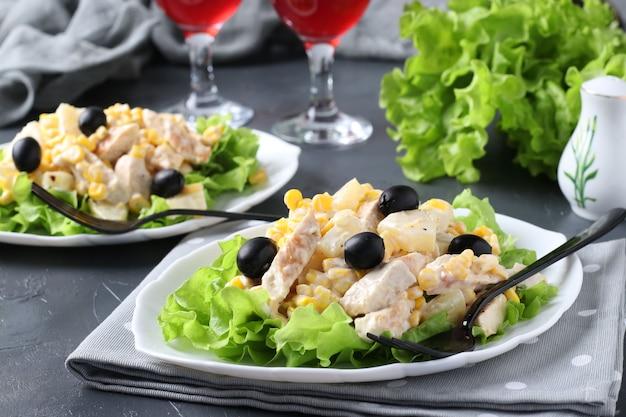 Zwei teller mit salatananas, gebackenem huhn, mais und schwarzen oliven und zwei gläsern rotwein, nahaufnahme