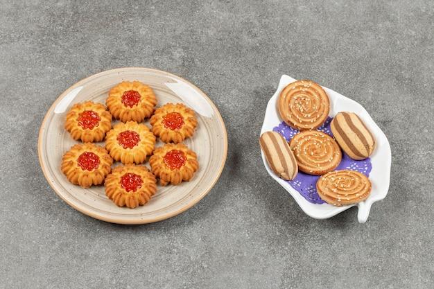 Zwei teller mit verschiedenen keksen auf marmoroberfläche