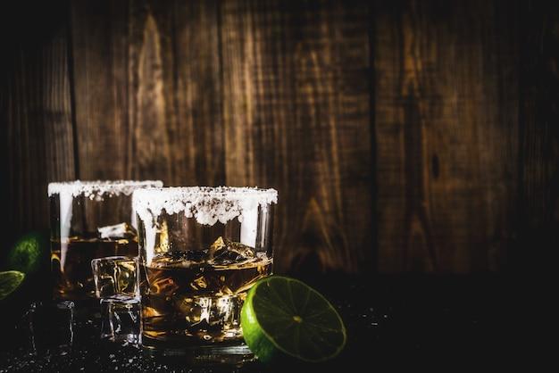 Zwei tequila-schnapsgläser auf dunklem hintergrund, mit eiswürfeln, salz und kalken