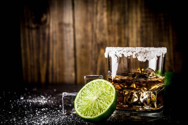 Zwei tequila-schnapsgläser auf dunklem tisch, mit eiswürfeln, salz und limetten