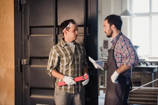 Zwei tischler unterhalten sich, während sie papiere und lineal halten. einer von ihnen trägt eine sicherheitsmaske. tischlerei
