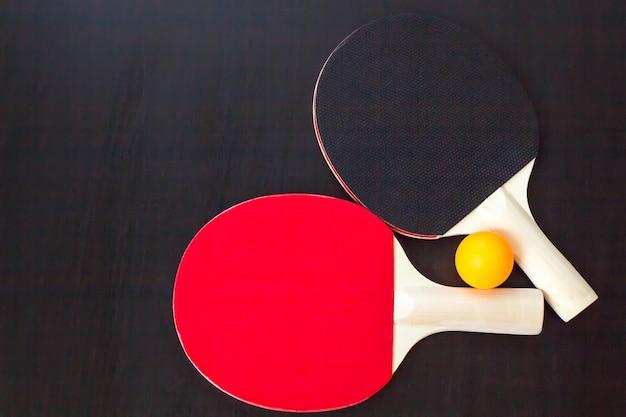 Zwei tischtennis oder ping-pong-schläger und ball auf einem schwarzen hintergrund