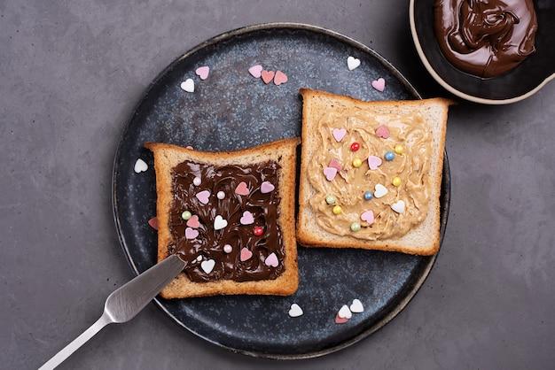 Zwei toast mit kakaoaufstrich und erdnussbutter, bestreut mit bunten herzen, schüssel mit schokoladenpaste auf grauem betonhintergrund.