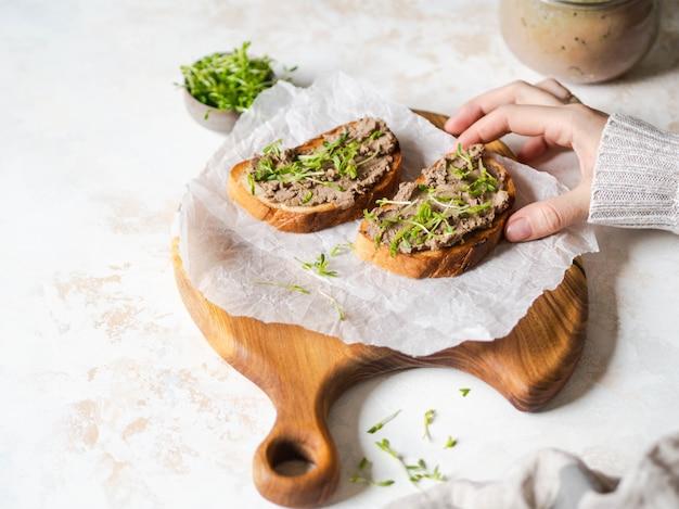 Zwei toasthuhn rillettes (pastete) auf weißbrot mit sprösslingen auf einem hölzernen schneidebrett und einer weiblichen hand nimmt toast auf marmor. copyspace
