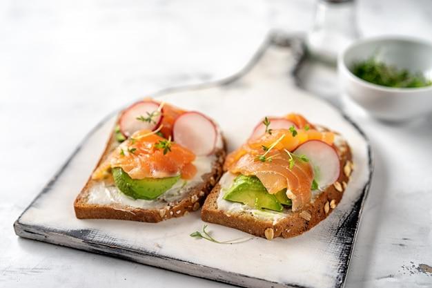 Zwei toasts mit avocado, rettich und lachs. gesundes essen
