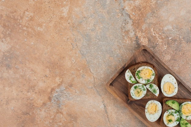 Zwei toasts mit gurke und gekochten eiern auf dem marmortisch.