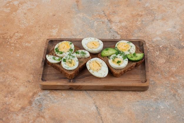 Zwei toasts mit gurke und gekochten eiern in der marmoroberfläche