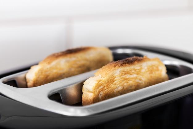Zwei toaststücke, die vom toaster herausspringen