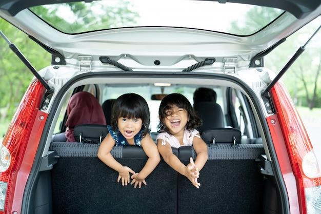 Zwei tochter spielen auf dem rücksitz des autos und schauen vom gepäck zurück