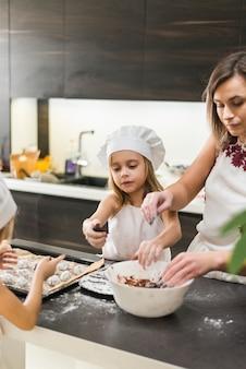 Zwei töchter und mutter, die plätzchen in der küche zubereiten