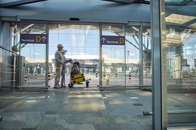 Zwei touristen mit gepäck am flughafen