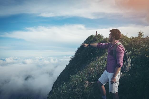 Zwei touristen mit rucksäcken sonnenuntergang auf einen berg genießen