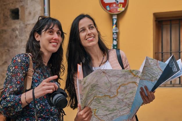 Zwei touristische mädchen, die im urlaub mit einer karte durch die straßen der stadt gehen