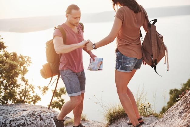 Zwei touristische männer und frauen mit rucksäcken klettern auf die spitze des berges und genießen den sonnenaufgang.
