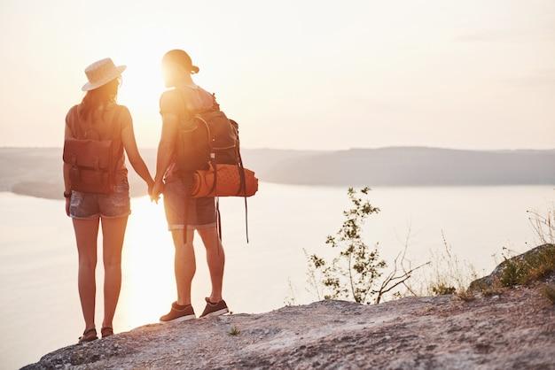 Zwei touristische männer und frauen mit rucksäcken stehen oben auf dem felsen und genießen den sonnenaufgang. reisen berge und küste, freiheit und aktives lifestyle-konzept