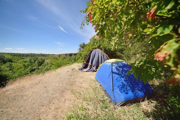 Zwei touristische zelte vor dem hintergrund der schönen landschaft und des grüns. camping