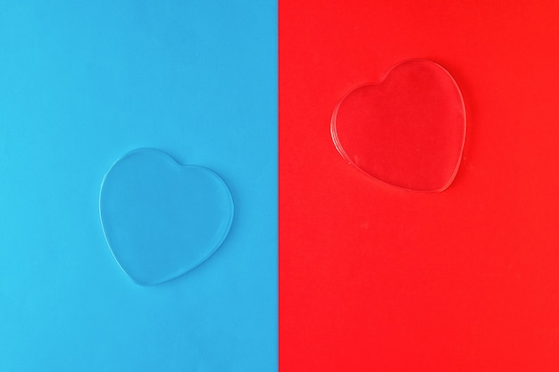 Zwei transparente herzen auf einer blauen und roten oberfläche