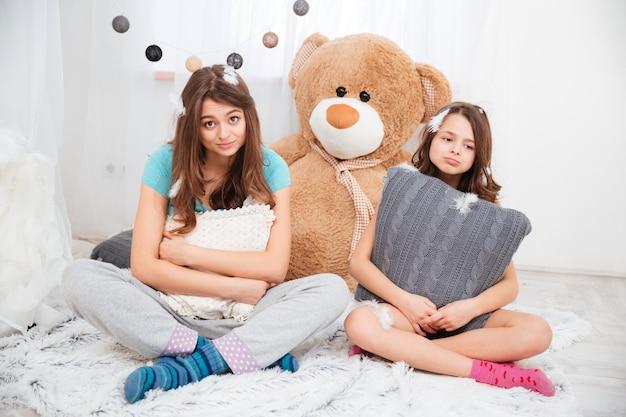 Zwei traurige müde schwestern, die zu hause kissen im kinderzimmer umarmen