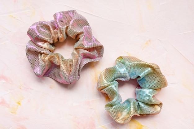 Zwei trendige holografische schillernde metallische haargummis auf rosa hintergrund. diy accessoires und frisuren konzept, kopierraum