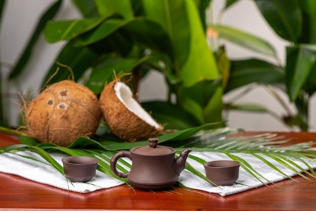Zwei tropische kokosnüsse, die nahe einer teekanne und zwei schalen für badekurorttherapie unter grüns und einer palmenniederlassung liegen