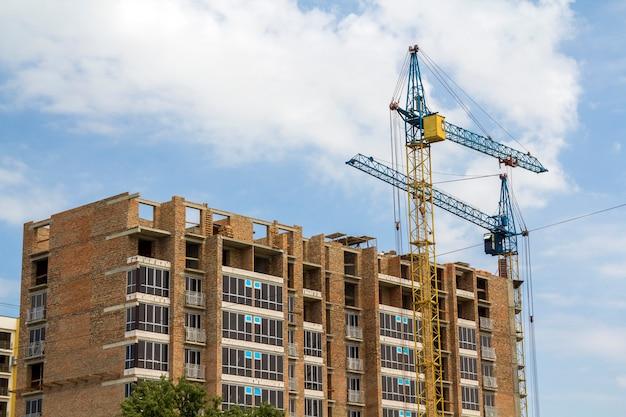 Zwei turmkrane, die im bau an hohem aufstiegsbacksteinbau auf blauer sonniger himmelkopien-raumszene arbeiten. moderne urbane architektur, investitionen, kauf- und verkaufskonzept.