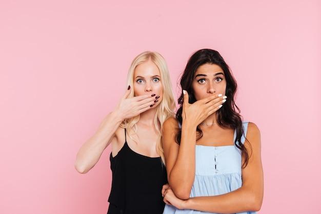 Zwei überraschte frauen bedecken ihren mund und schauen in die kamera