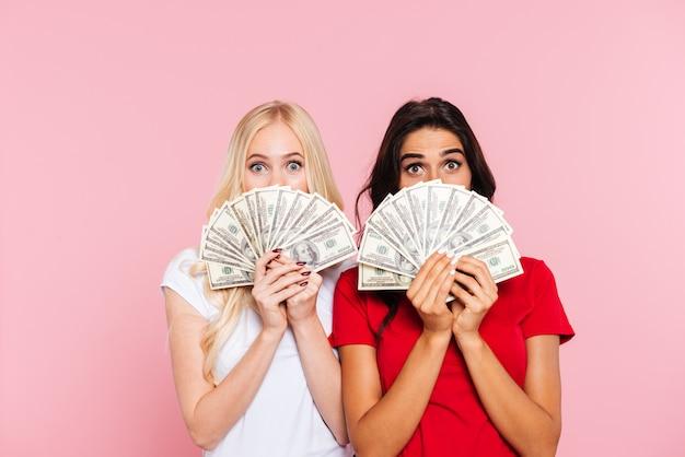 Zwei überraschte frauen, die sich hinter dem geld verstecken und über pink in die kamera schauen